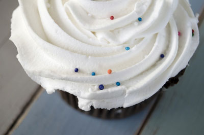 The texture of the faded colored wood tray under this cupcake adds interest. [Credit: Focal length: